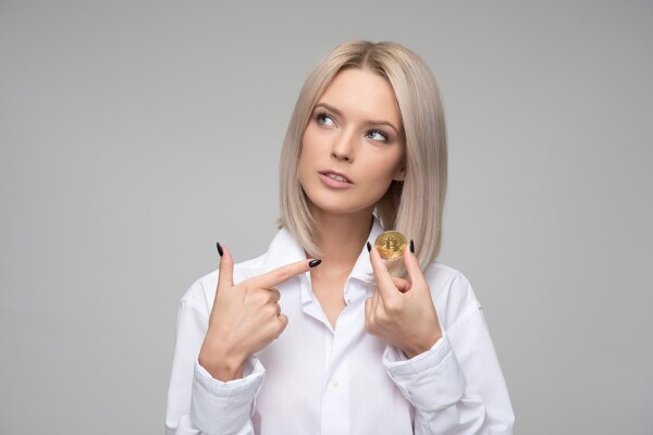 woman pointing to a bitcoin
