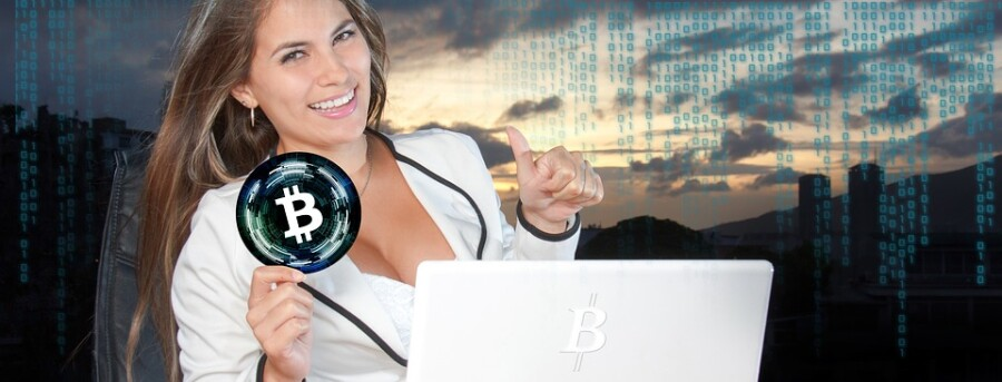 lady grabbing bitcoin in front of laptop