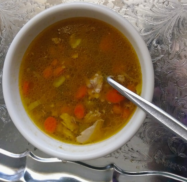 Chicken vegetable soup in white bowl