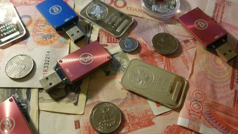 USB miners ontop of Japanese Yen, Chinese Yuan, USD, and Silver bars
