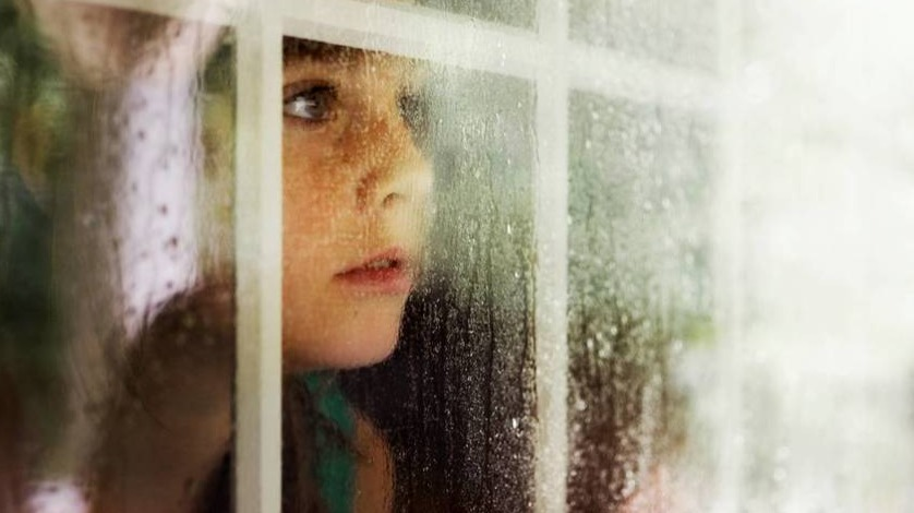 Child looking through a window