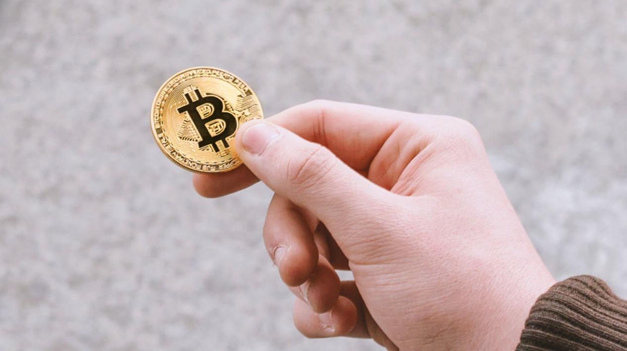 man's hand holding bitcoin