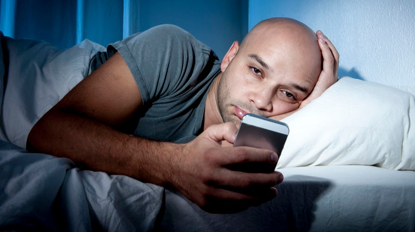 Man using smartphone in bed realizing he needs to quit social media and stop using it so much