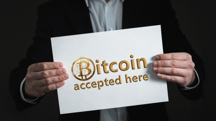 """Man holding sign that reads """"bitcoin accepted here"""""""