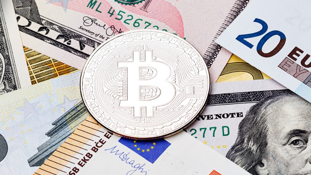 bitcoin on top of dollar and euro bills
