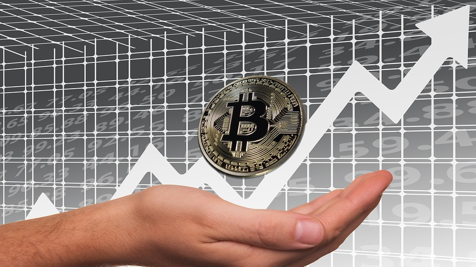 bitcoin on a hand in front of an ascending arrow