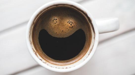 filled coffee mug where the coffee foam looks like a crazy happy face