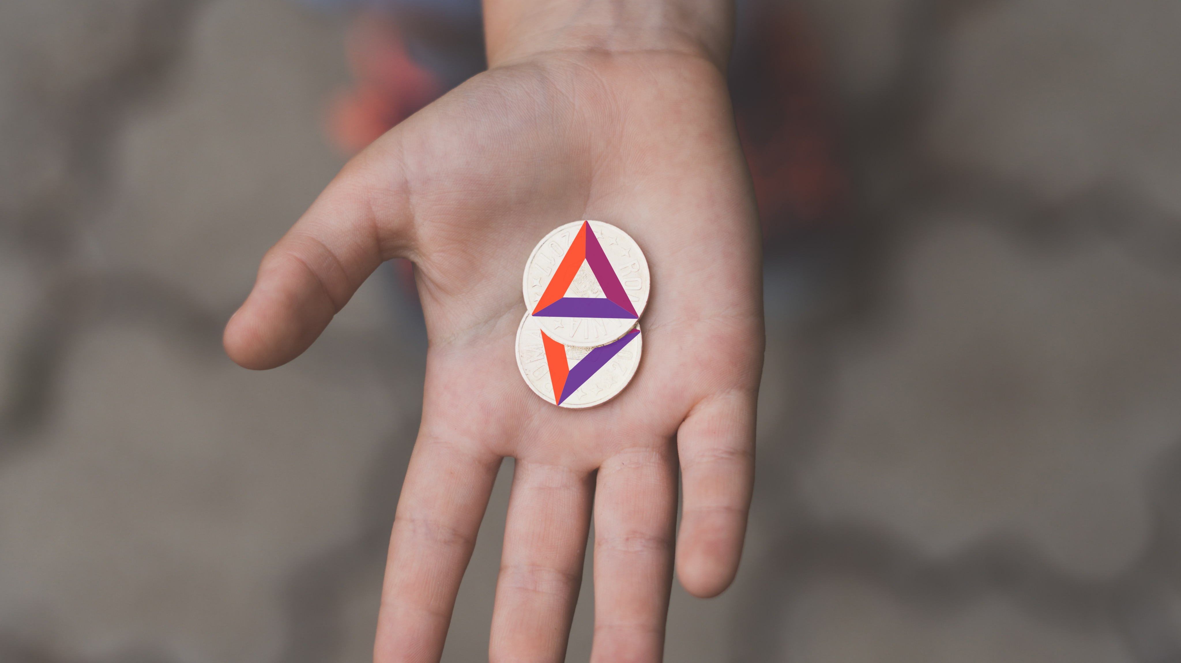 Hand offering up some coins with the BAT logo on them.